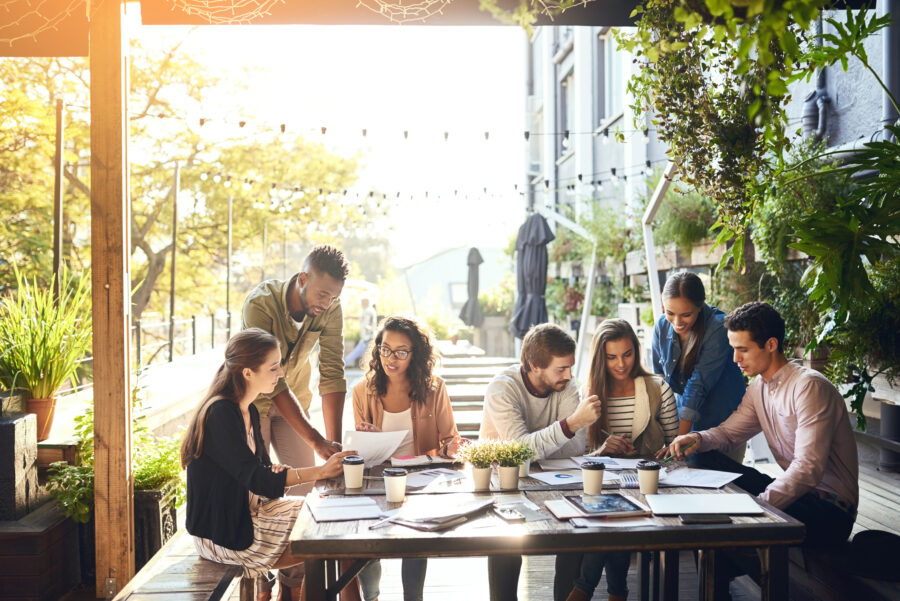 Millennials working together on outdoor patio of coffee shop