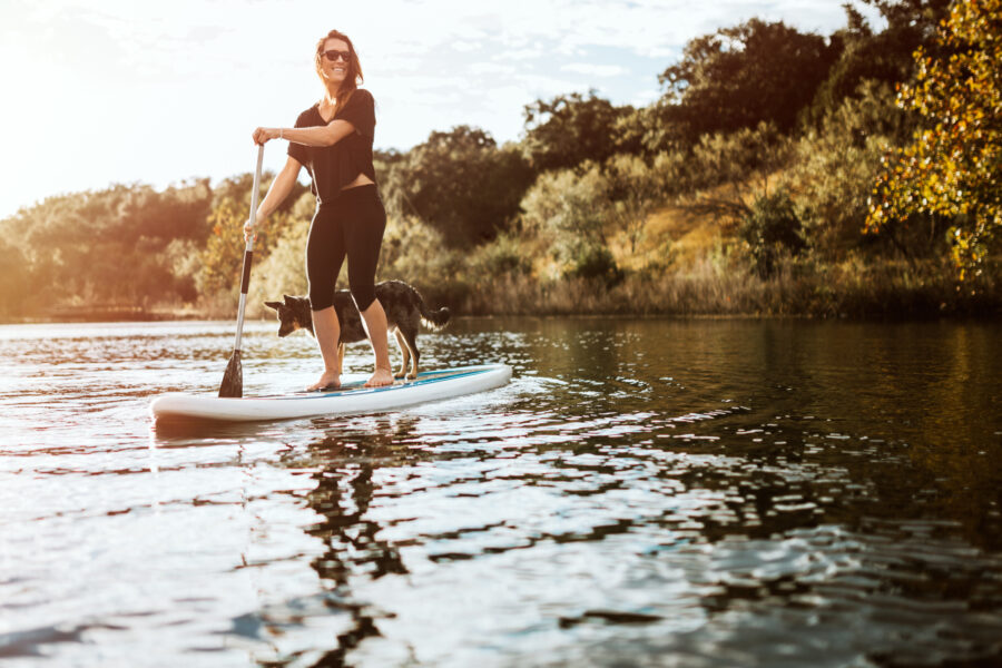 Woman on stand-up paddle with dog on the lake