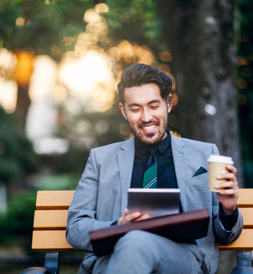Business man wearing suit and sitting on park bench with iPad and coffee