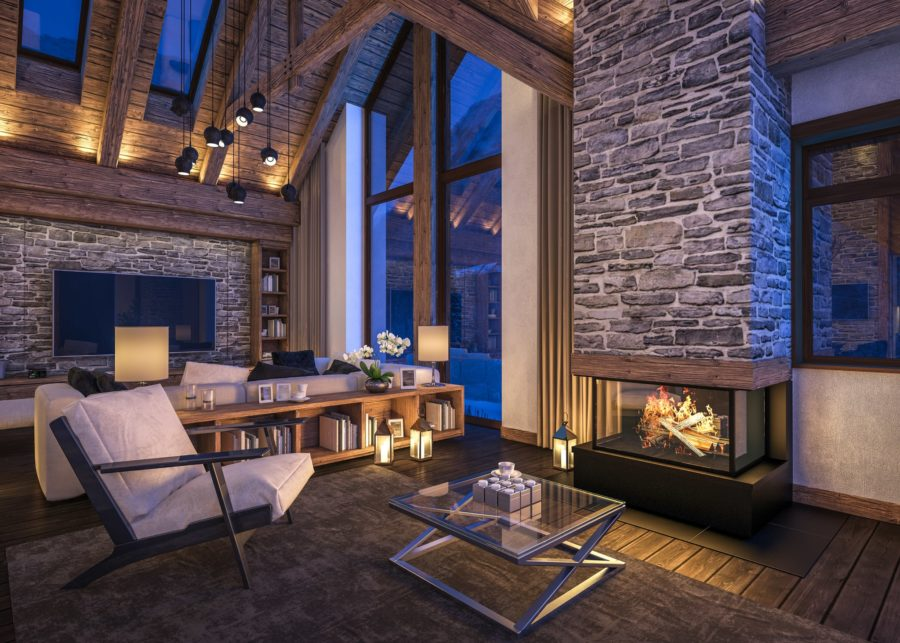Interior of modern rustic cabin-style living room with large windows, exposed stone, and fireplace