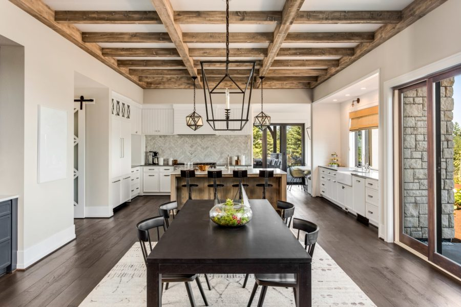 Interior view of modern farmhouse style kitchen and dining area with exposed beams and contemporary furniture
