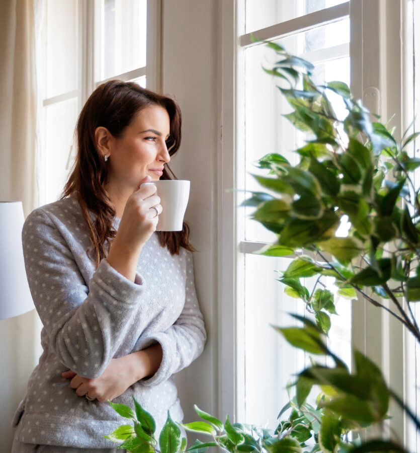 Woman at home drinking coffee and enjoying lake views from window
