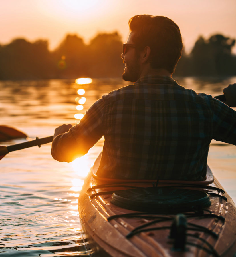 man kayaking on lake at sunset